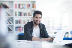 Estudiante en biblioteca escolar usando el ordenador portátil para la investigación Fotos de archivo libres de regalías