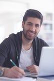 Estudiante en biblioteca escolar usando el ordenador portátil para la investigación Foto de archivo
