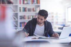 Estudiante en biblioteca escolar usando el ordenador portátil para la investigación Imagen de archivo libre de regalías
