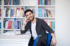 Estudiante en biblioteca escolar usando el ordenador portátil para la investigación Imágenes de archivo libres de regalías