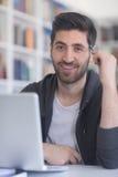 Estudiante en biblioteca escolar usando el ordenador portátil para la investigación Fotografía de archivo libre de regalías