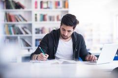 Estudiante en biblioteca escolar usando el ordenador portátil para la investigación Foto de archivo libre de regalías