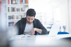 Estudiante en biblioteca escolar usando el ordenador portátil para la investigación Fotos de archivo