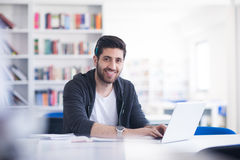 Estudiante en biblioteca escolar usando el ordenador portátil para la investigación Fotografía de archivo