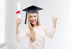 Estudiante en casquillo de la graduación con el certificado Imagen de archivo libre de regalías
