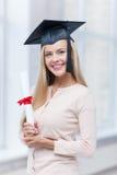 Estudiante en casquillo de la graduación con el certificado Imagenes de archivo