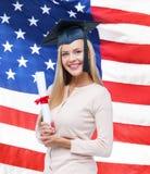 Estudiante en casquillo de la graduación con el certificado Foto de archivo libre de regalías