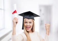 Estudiante en casquillo de la graduación con el certificado Foto de archivo
