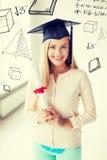 Estudiante en casquillo de la graduación con el certificado Fotos de archivo