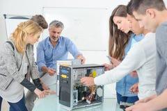Estudiante en el entrenamiento del curso de la ingeniería eléctrica con el profesor foto de archivo libre de regalías