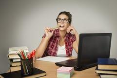 Estudiante en el ordenador portátil, muchacha que estudia, libros de la universidad del ordenador fotografía de archivo