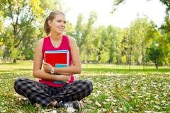 Estudiante en el parque que abraza los libros Fotos de archivo libres de regalías