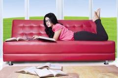 Estudiante en el sofá con el ordenador portátil y los libros Imagenes de archivo