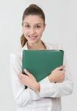 Estudiante en la camisa blanca con la carpeta verde que mira a la cámara Imagen de archivo libre de regalías