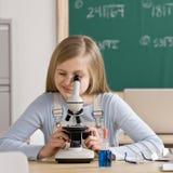 Estudiante en la sala de clase que mira con fijeza en el microscopio Fotos de archivo libres de regalías
