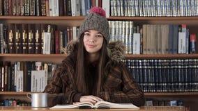 Estudiante en la tabla de la universidad con el libro de texto metrajes