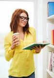 Estudiante en lentes con el libro y el café Foto de archivo