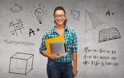 Estudiante en lentes con las carpetas y PC de la tableta Imagen de archivo libre de regalías