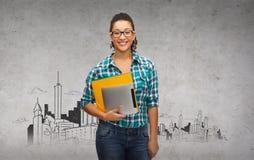 Estudiante en lentes con las carpetas y PC de la tableta Foto de archivo libre de regalías