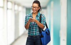 Estudiante en lentes con smartphone y el bolso Fotografía de archivo