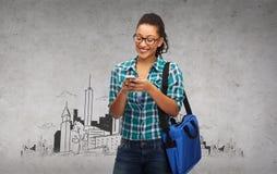 Estudiante en lentes con smartphone y el bolso Fotografía de archivo libre de regalías