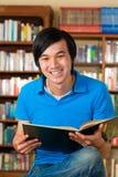 Estudiante en libro de lectura de la biblioteca Foto de archivo libre de regalías