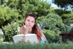 Estudiante en parque con el libro que mira para arriba Imagenes de archivo