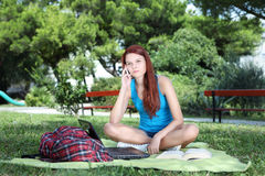 Estudiante en parque con el libro y el ordenador que habla en el teléfono celular Fotos de archivo libres de regalías