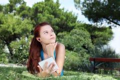 Estudiante en parque con el libro y los auriculares digitales Fotos de archivo libres de regalías