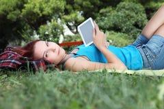 Estudiante en parque con el libro y los auriculares digitales Foto de archivo libre de regalías