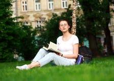 Estudiante en parque de la ciudad con el libro Imagenes de archivo