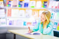 Estudiante en una biblioteca Fotografía de archivo libre de regalías
