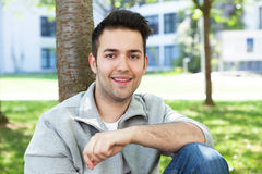 Estudiante en una chaqueta gris en el campus que mira la cámara Fotografía de archivo