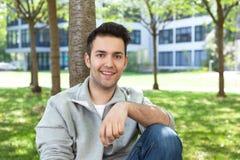 Estudiante en una chaqueta gris que se relaja en el campus Fotografía de archivo