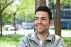 Estudiante en una chaqueta gris que sueña en el campus Imágenes de archivo libres de regalías