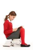 Estudiante en uniforme en la pila de libros fotos de archivo