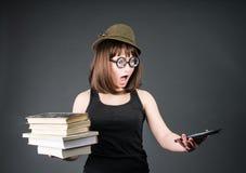 Estudiante en vidrios divertidos con los libros viejos en un mano y e-lector en otro en fondo gris La muchacha del empollón está  Imagen de archivo libre de regalías