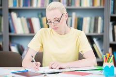 Estudiante en vidrios que escribe en biblioteca Fotografía de archivo libre de regalías