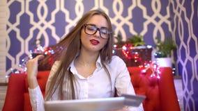 Estudiante en vidrios usando la tableta para en la línea compra con la tarjeta de crédito 4K Mujer que usa el ordenador de la PC  almacen de video