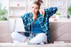 Estudiante encadenado con el ordenador portátil que se sienta en el sofá Fotos de archivo libres de regalías