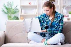 Estudiante encadenado con el ordenador portátil que se sienta en el sofá Foto de archivo libre de regalías