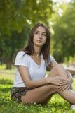 Estudiante encantador Girl Sitting en hierba verde fotografía de archivo libre de regalías