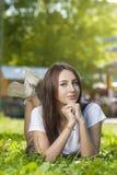 Estudiante encantador Girl Sitting en hierba verde fotos de archivo