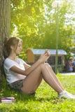 Estudiante encantador Girl Sitting en hierba verde foto de archivo