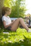 Estudiante encantador Girl Sitting en hierba verde imágenes de archivo libres de regalías