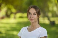 Estudiante encantador Girl Sitting en hierba verde fotos de archivo libres de regalías