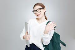 Estudiante encantadora alegre que sostiene el ordenador portátil y que agita con la mano Imágenes de archivo libres de regalías