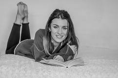 Estudiante encantadora joven con el pelo largo que miente en la cama que lee un libro y que se prepara para las clases Imagen de archivo