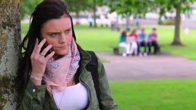 Estudiante enfadado que se inclina contra un árbol que hace una llamada de teléfono almacen de metraje de vídeo