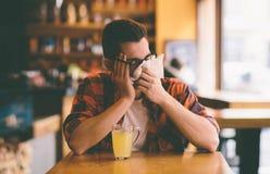 Estudiante enfermo que sopla su nariz en un tejido Imagen de archivo